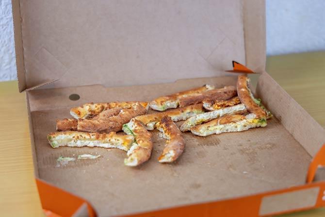 Pizzakarton mit Essensresten